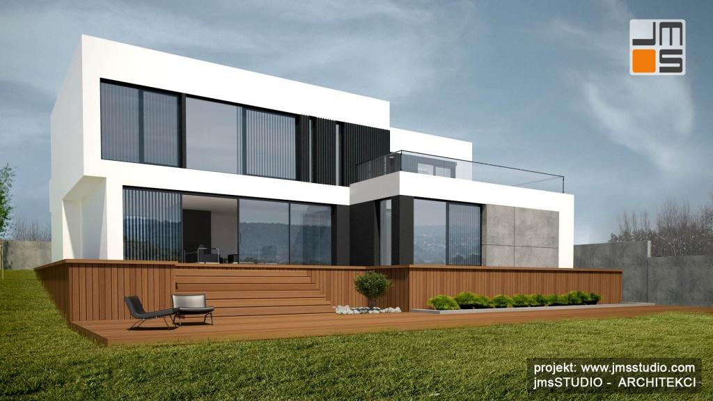 Projekt nowoczesnego energooszczędnego domu z dużymi oknami, prostą geometryczną elewacją i dużym tarasem na działce ze spadkiem pod Krakowem