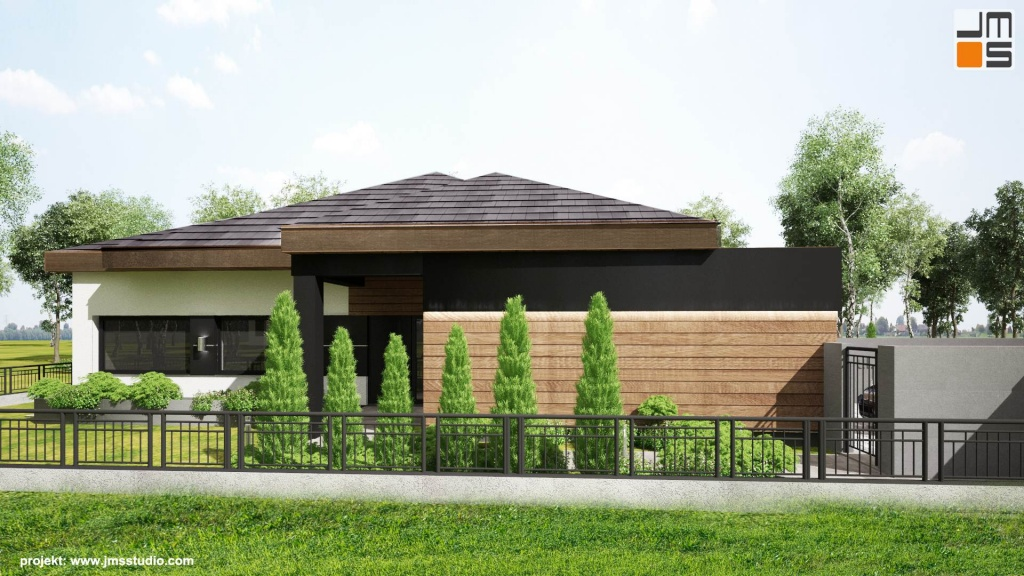 Frontowa elewacja budynku willi na Śląsku została zaprojektowana w taki sposób by stworzyć ciekawe i designerskie połączenie ciepłego koloru drewna z chłodnym kolorem antracytowym i białym tynkiem.