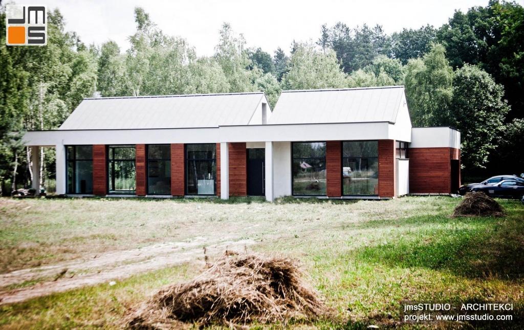 nowoczesny projekt prostego domu z dużymi przeszkleniami drewnem na elewacji i blachą na rąbek na dachu pod Brzeskiem