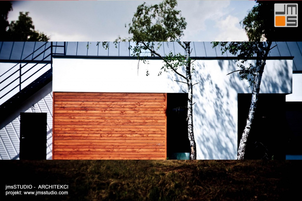w nowoczesnym projekcie domu zestawiono ze sobą drewno elewacyjne szarą blachę i biały tynk tworząc designerski dom
