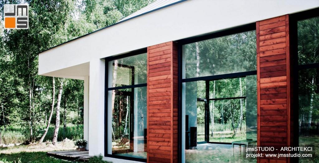 Zdjęcia z realizacji nowoczesnego projektu domu z dużym przeszkleniami i drewnem na elewacji oraz dachem z blachy na rąbek pod Brzeskiem