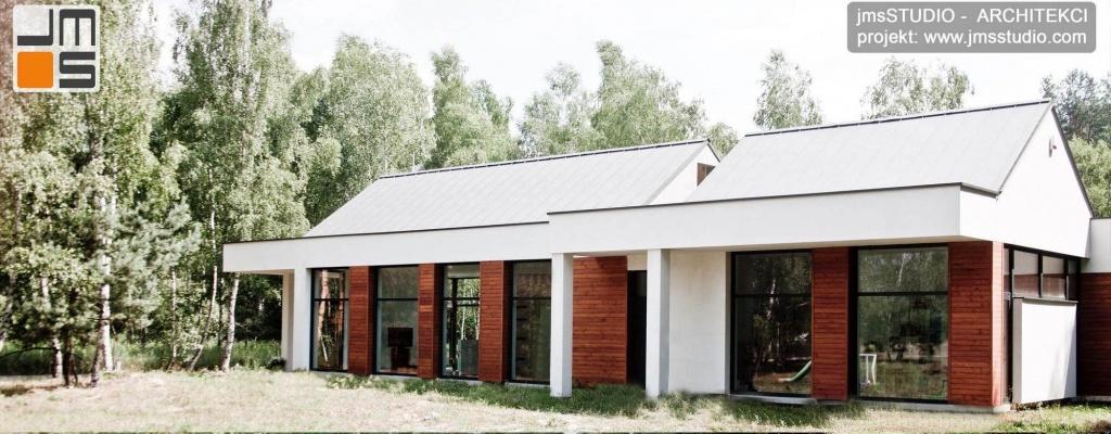 Zdjęcia z realizacji nowoczesnego projektu domu z dużymi przeszkleniami i drewnem na elewacji oraz dachem z blachy na rąbek pod Brzeskiem