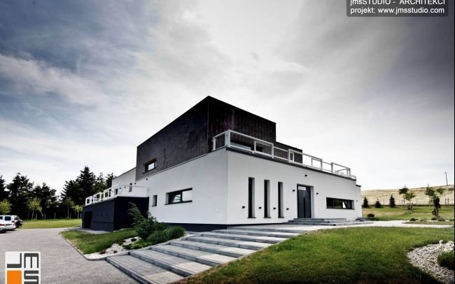 Architekt Kraków - Indywidualny projekt dużego prostego i nowoczesnego domu z płaskim dachem i pomysłem na elewacje z gresem na działce ze spadkiem pod Poznaniem