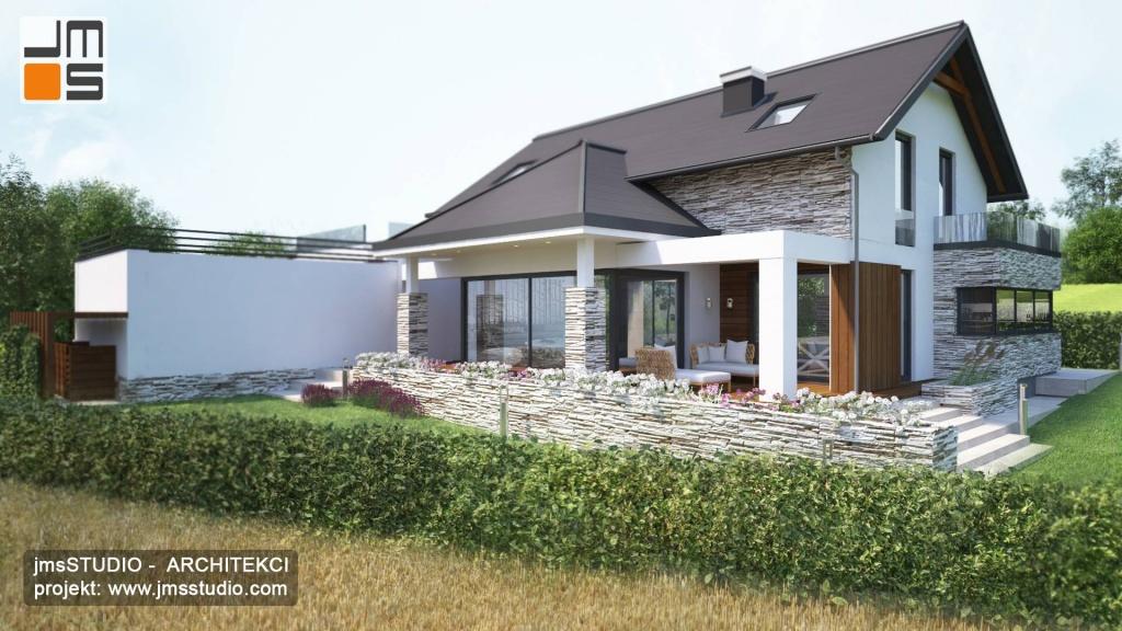 Od strony ogrodu nowoczesnego domu zaprojektowano piękny zadaszony taras, oddzielony od ogrodu murem kamiennym