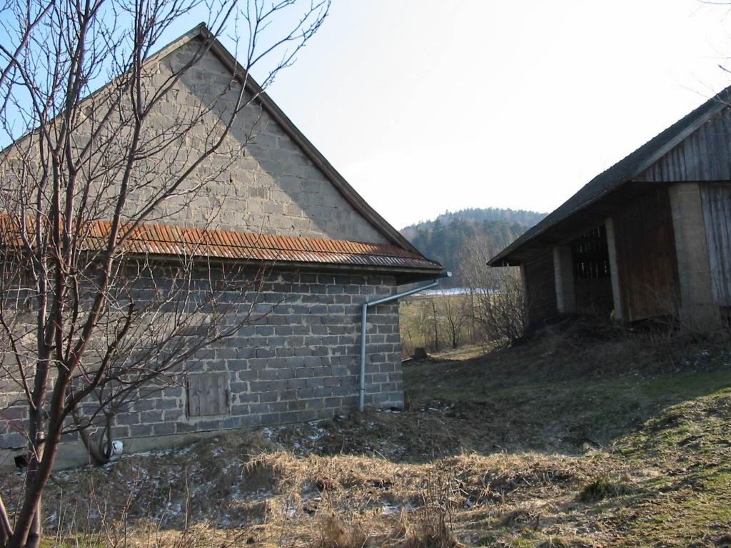 Siedlisko w górach. Dom i stodoła przed przebudową i rozbudową widać że działka ma duży spadek który wymaga dobrego projektu