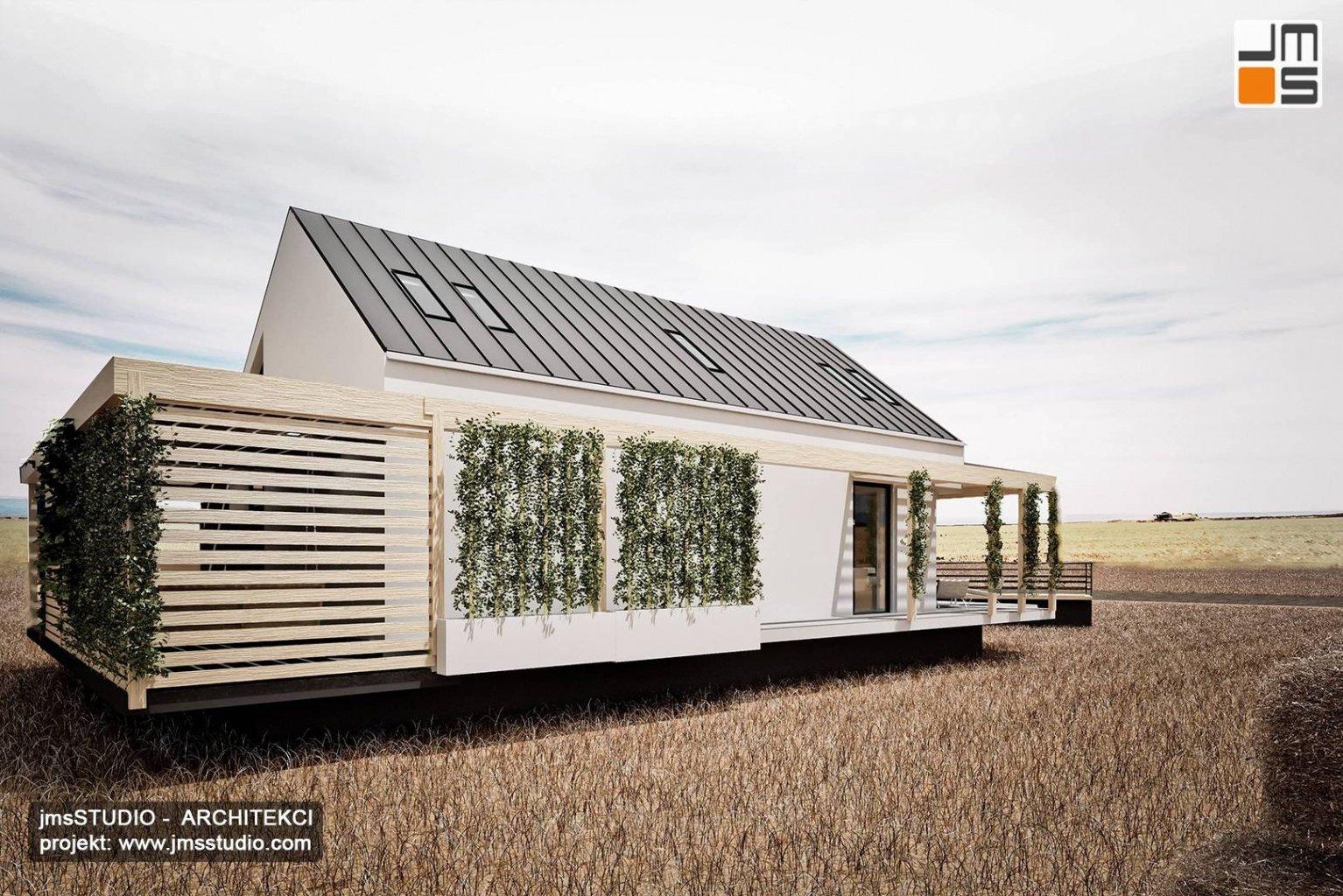 Dom modułowy z zieloną ścianą i pergolą oraz żaluzjami przeciwsłonecznymi to projekt domu architekt Śląsk