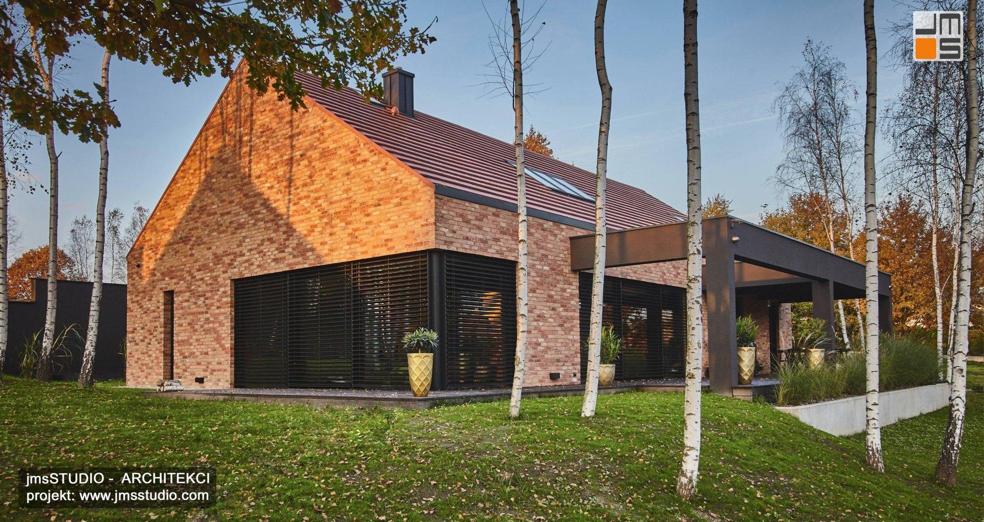 Indywidualny projekt domu z elewacją z cegły z żaluzjami zewnętrznymi dużymi oknami antracytowymi i ciekawym pomysłem na drewniany taras z dekoracyjną ramą - zdjęcia z realizacji